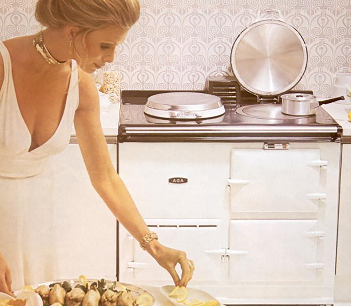1970 AGA advert featuring a lady in white cooking on a white AGA